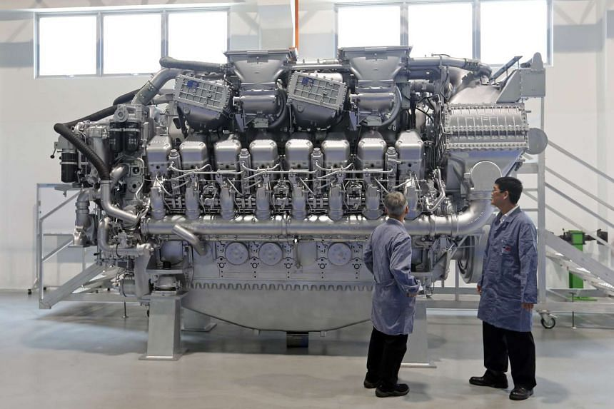 Staff at the new headquarters building with a high-speed diesel engine for marine use.