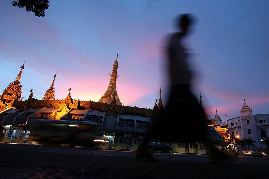 A pedestrian walks past the Sule Pagoda in Yangon on June 3, 2013.