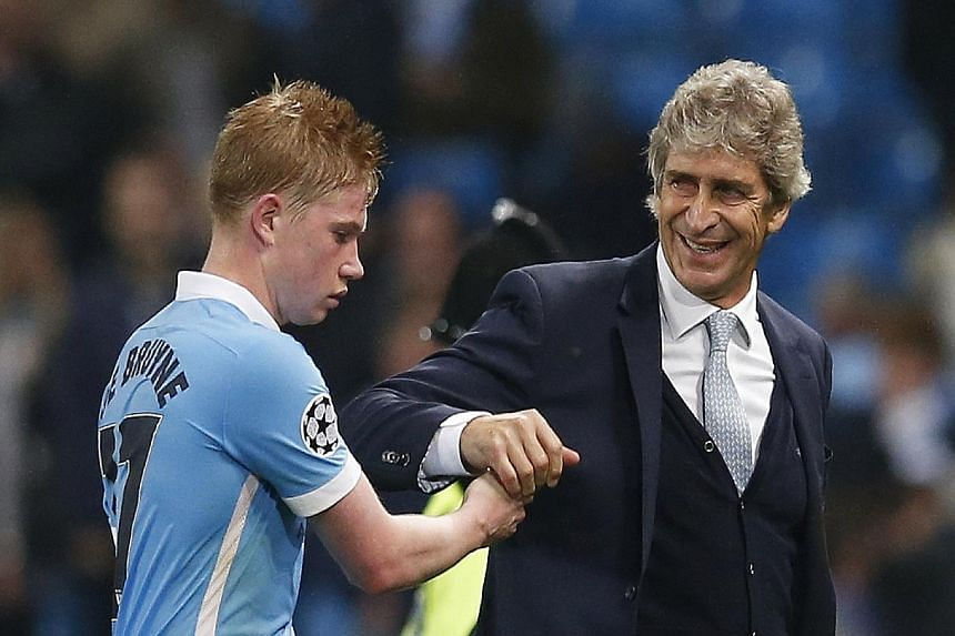 Manchester City's Kevin de Bruyne congratulated by manager Manuel Pellegrini. The club-record signing scored a dramatic stoppage-time winner against Sevilla to seal a 2-1 win.
