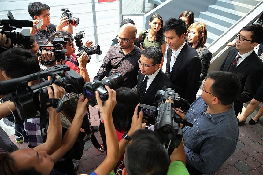 Lawyer Edwin Tong (facing the media, with tie), Kong Hee (behind Mr Tong) and Kong's wife Ho Yeow Sun (behind Kong) leaving the courts on Wednesday. Kong and five others were on Wednesday convicted of misusing some $50 million in City Harvest Church
