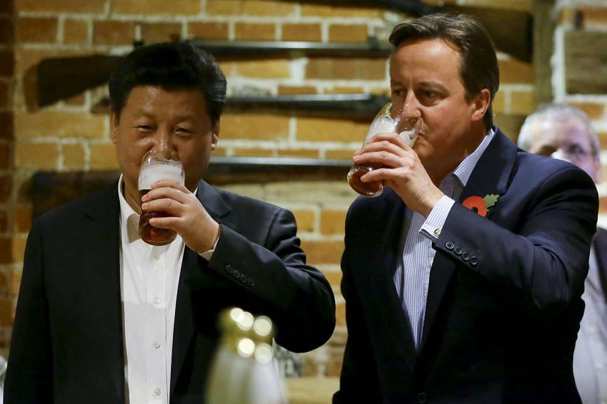 Britain's Prime Minister David Cameron (right) drinks beer with Chinese President Xi Jinping at a pub near the PM's official country residence Chequers.