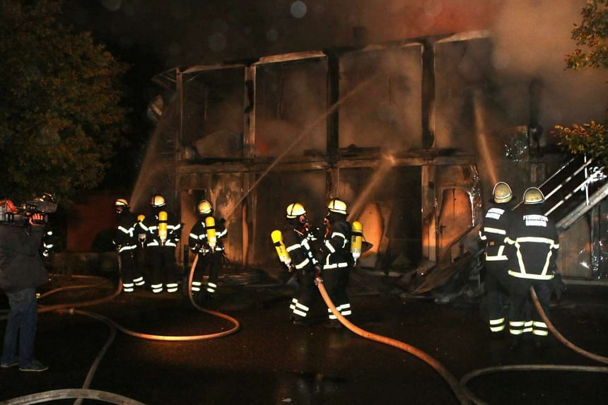 Firefighters extinguishing a blaze at a refugee accommodation centre in the Suelldorf area of Hamburg, Germany.