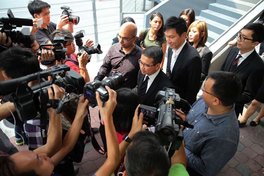 Lawyer Edwin Tong (centre) speaking to the media in front of church founder Kong Hee and his wife Ho Yeow Sun as they leave the State Courts on Oct 21, 2015.
