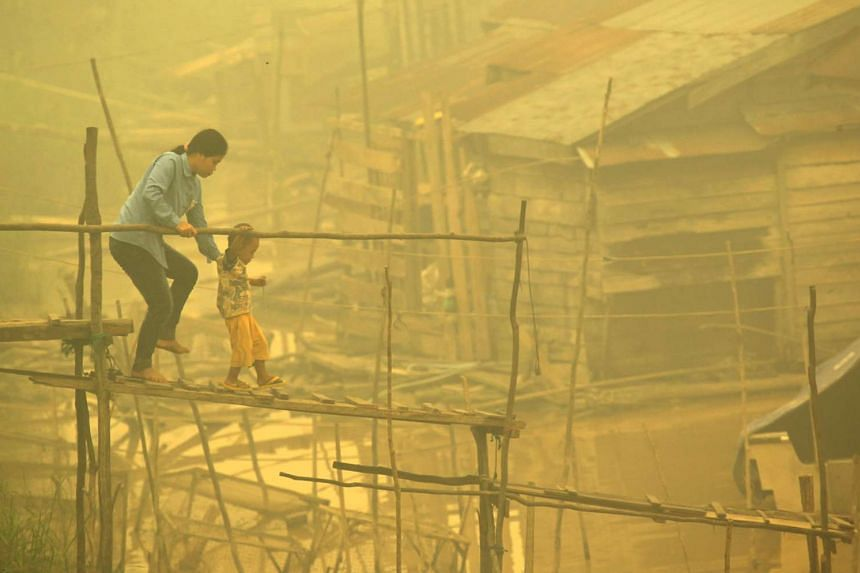 An Indonesian woman and child walk on a bamboo bridge as thick yellow haze shrouds the city in Palangkaraya on Oct 22, 2015.