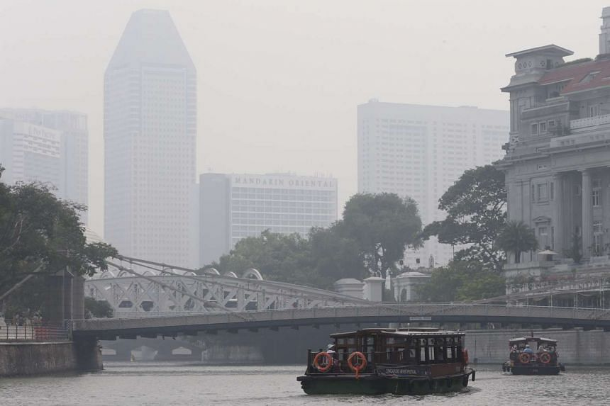 Tourists taking a Singapore River cruise on Friday (Oct 23) at 9.30am against a backdrop of haze.