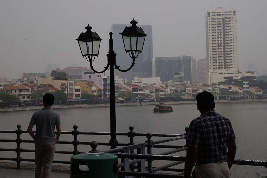 Members of the public taking in the scenery along Boat Quay on a hazy Friday (Oct 23) at 9.30am.