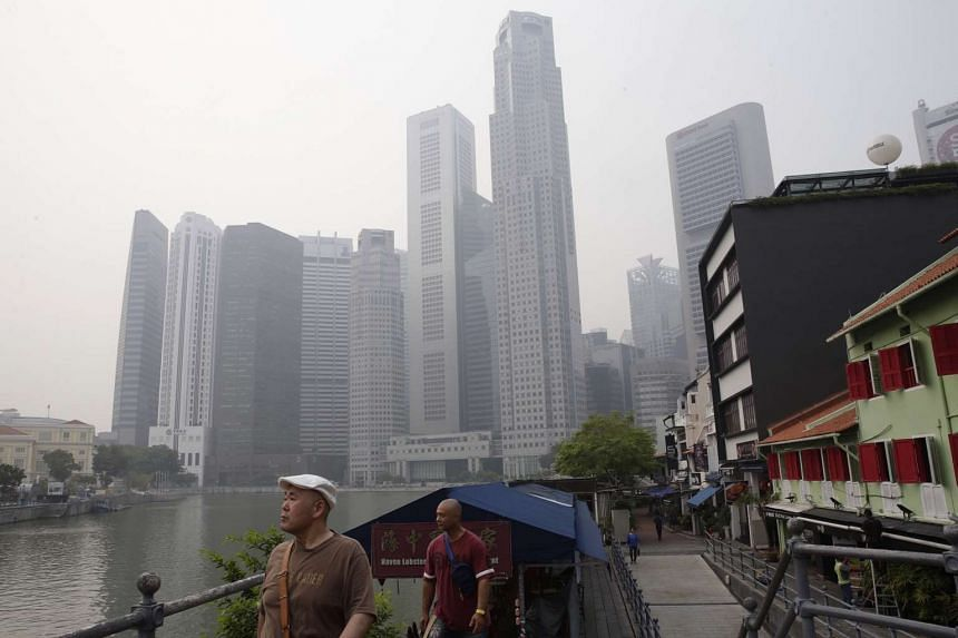 Tourists seen along Boat Quay on Friday (Oct 23) at 9.30am under hazy skies.