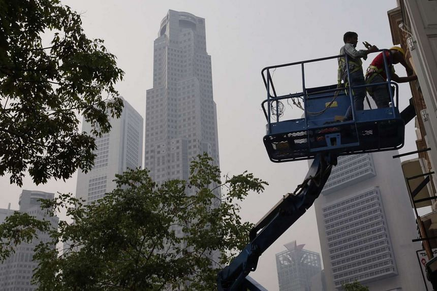 Workers on a cherry picker seen on Friday (Oct 23) at 9.30am in the haze.