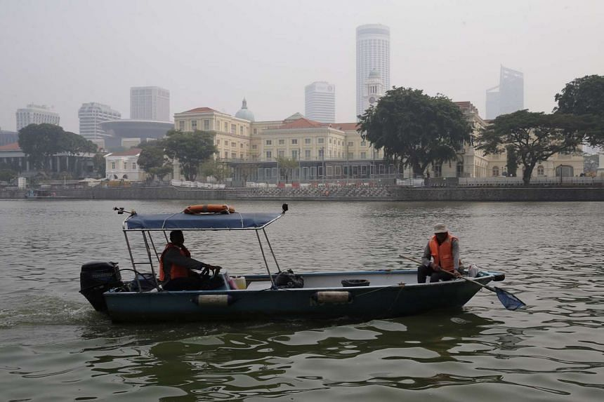 Workers on a boat cleaning the Singapore River on Friday (Oct 23) at 9.30am in hazy conditions.