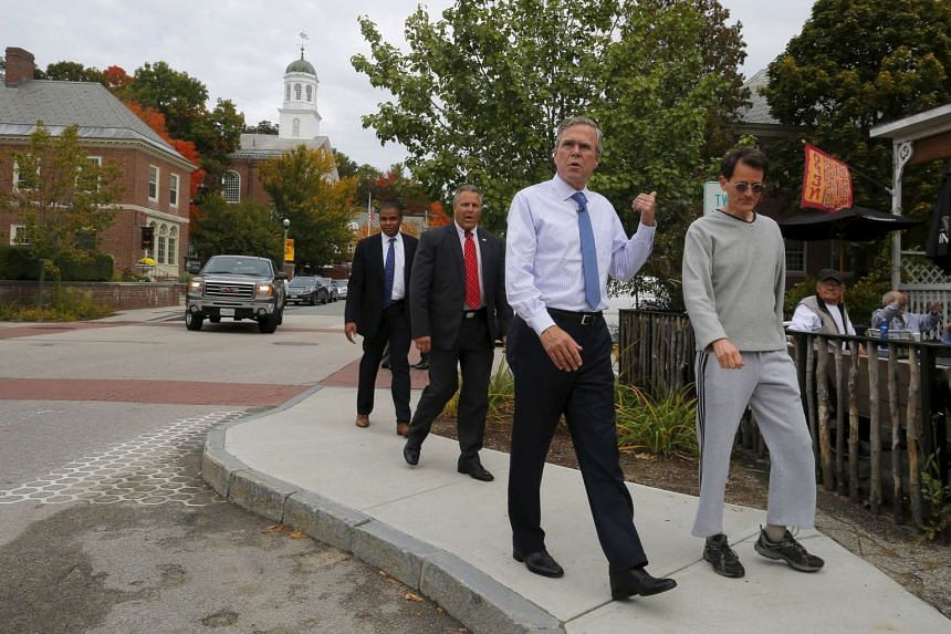 Jeb Bush walks with local resident Tracy Messer (right) through Peterborough, New Hampshire on Oct 13, 2015.