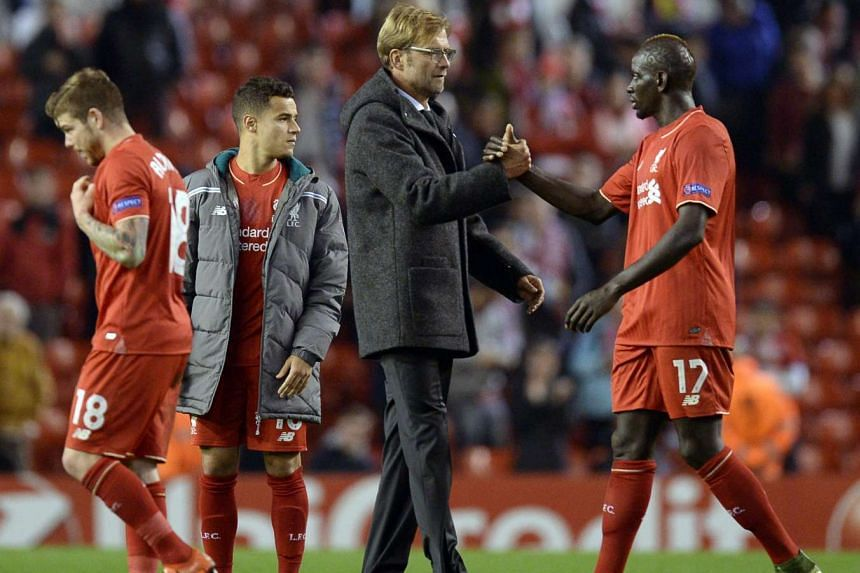Klopp (centre) taps hands with Liverpool's French defender Mamadou Sakho (right) after the match.