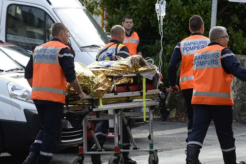 Emergency services personnel take away an injured person from the site of the collision on Oct 23, 2015 near Libourne, southwestern France.