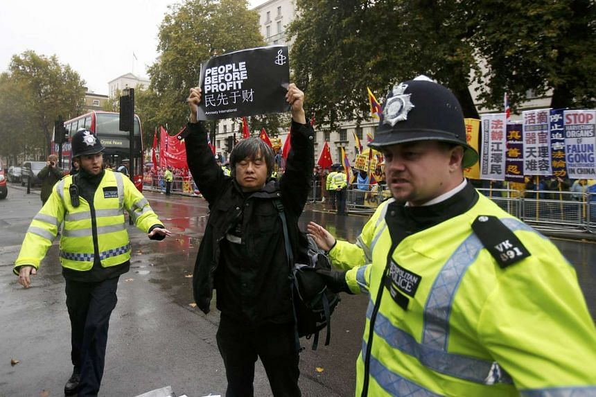 Police officers approach a man holding up a poster as he demonstrates against China's President Xi Jinping outside Downing Street in central London, Britain, Oct 21, 2015.