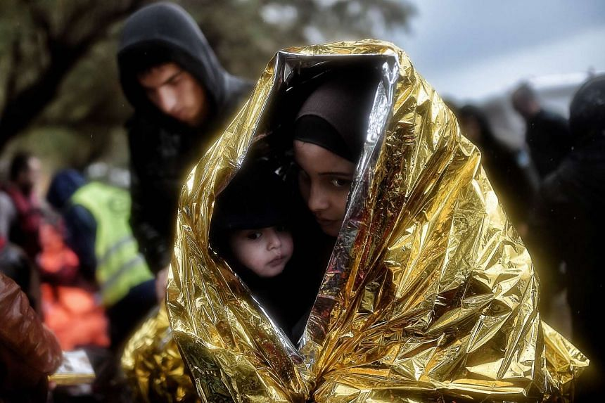 Children huddle inside emergency blankets as they arrive with other refugees and migrants on the Greek Island of Lesbos.