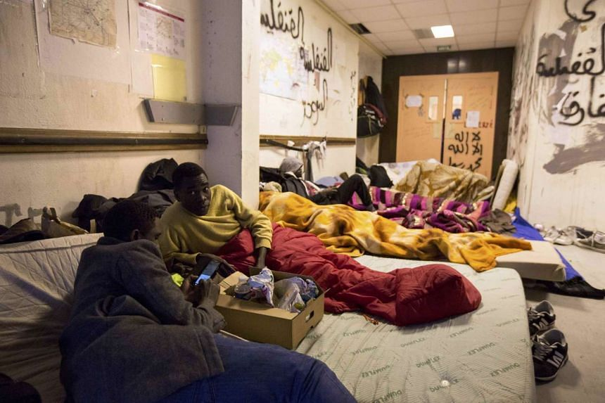 Migrants rest in a corridor of the Lycee Jean Quarre, a secondary school occupied by hundreds of migrants and asylum seekers since last August.