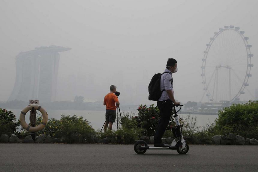 A masked man on his electric scooter rides past a man taking photographs of a hazy skyline from Gardens by the Bay East at 6pm on Oct 23, 2015.