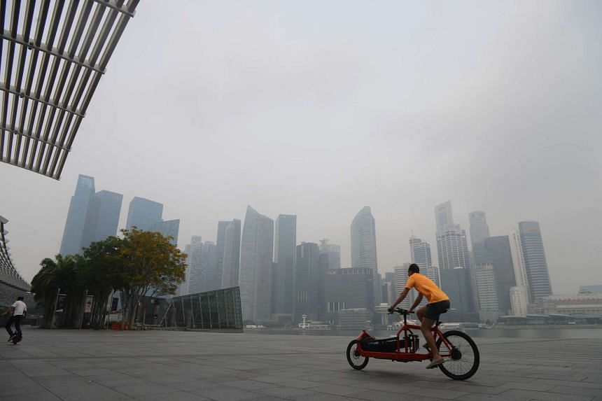 A man cycles past Marina Bay Sands with the Central Business District on the morning of 25th Oct, 2015.