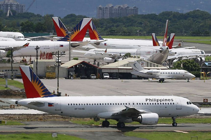 A Philippine Airlines (PAL) aircraft taxis on a runway at Manila International Airport.