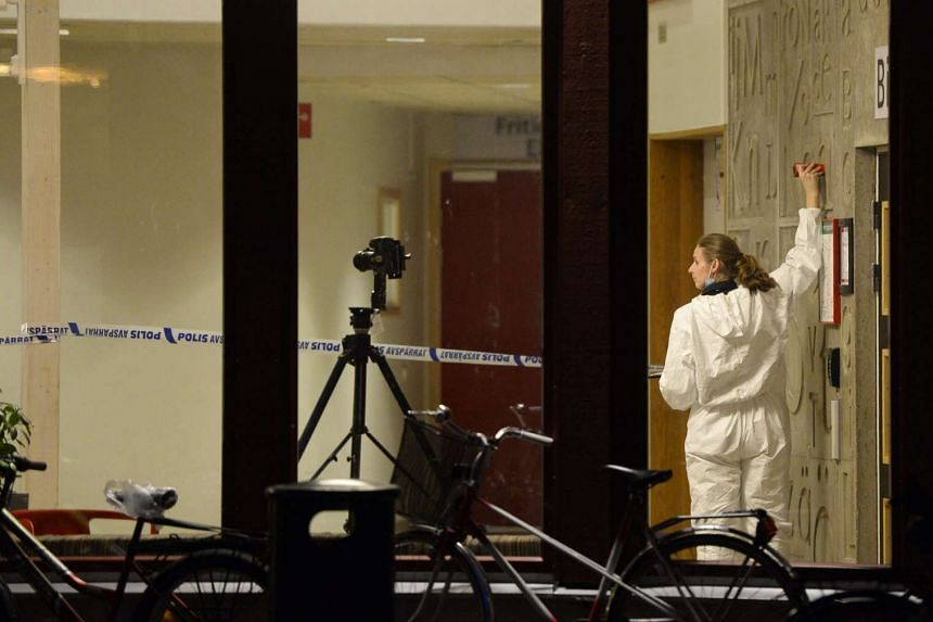 Forensic officers investigate at the school in Trollhattan, southwestern Sweden where a man armed with a sword killed a teacher and child and seriously wounded two others before being shot by police.
