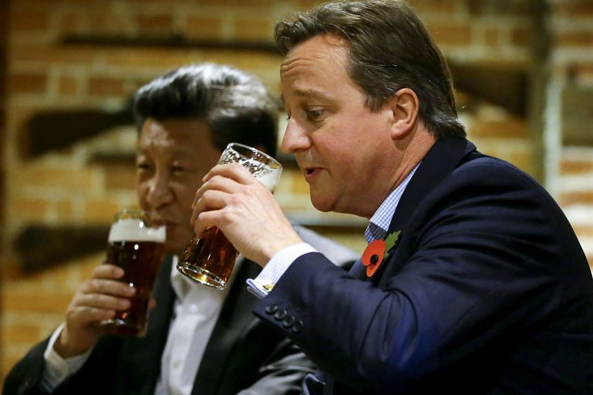Cameron (right) and Xi enjoy a pint at The Plough at Cadsden, near the British Prime Minister's official country residence.