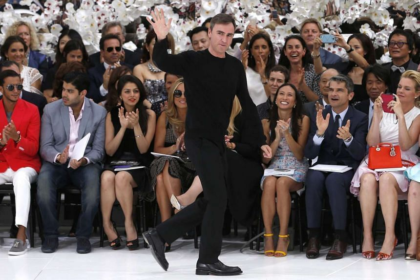 Belgian designer Raf Simons waves after presenting his Haute Couture Fall-Winter 2014/15 collection for Christian Dior.
