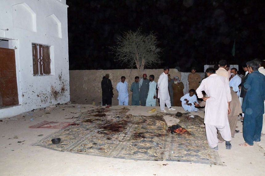 Pakistani Shi'ite Muslims gather at a mosque after a suicide bomb attack in the town of Chalgari, in restive Baluchistan.