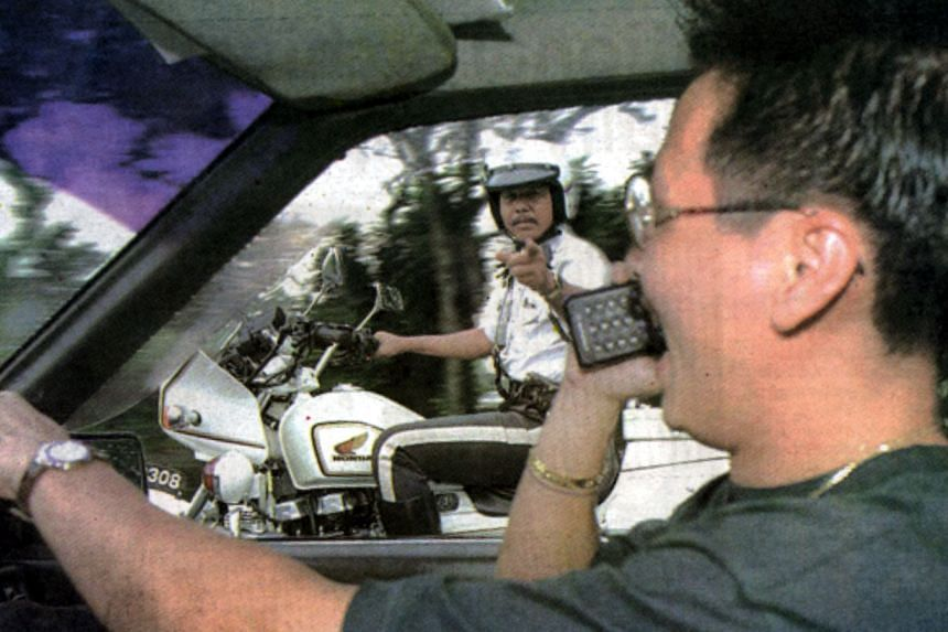 A traffic policeman gestures in warning to a driver on the handphone.