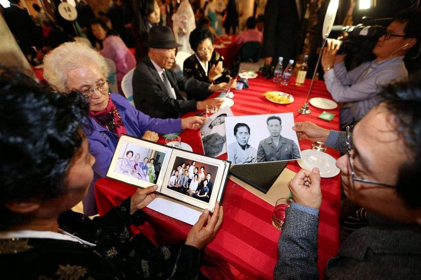South Korean and North Korean separated residents look at their family pictures during a luncheon on the first day of separated families reunion of second group on Mount Kumgang, Kangwon Province, North Korea, 24 Oct 2015.