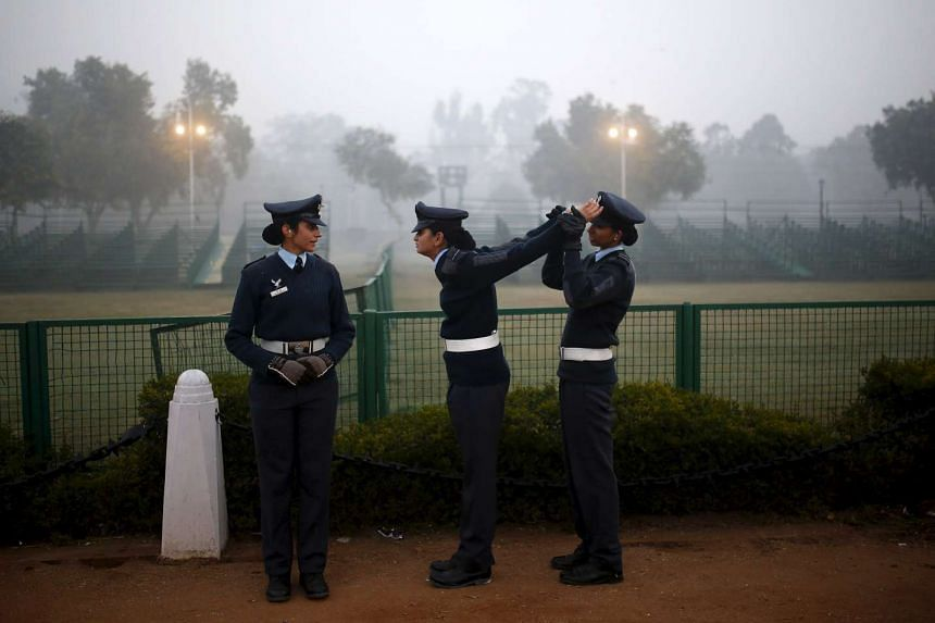 An Indian Air Force soldier (Right) stretches the arms of her colleague during the rehearsal for the Republic Day parade.