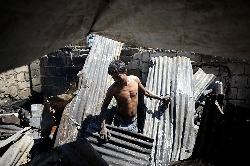 A resident stands among the broken remains of his house, which was gutted after an overnight fire tore through a slum area in Quezon City, Metro Manila, yesterday. The blaze left a scene of devastation in its wake. One hundred houses were destroyed i