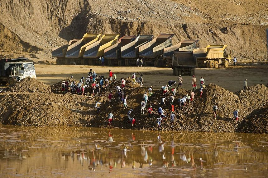 Miners on Oct 4 digging for raw jade stones in piles of waste rubble dumped by mechanical diggers next to a jade mine in Hpakant. The long-running conflict between Kachin and government forces is as much over natural resources as over political and e