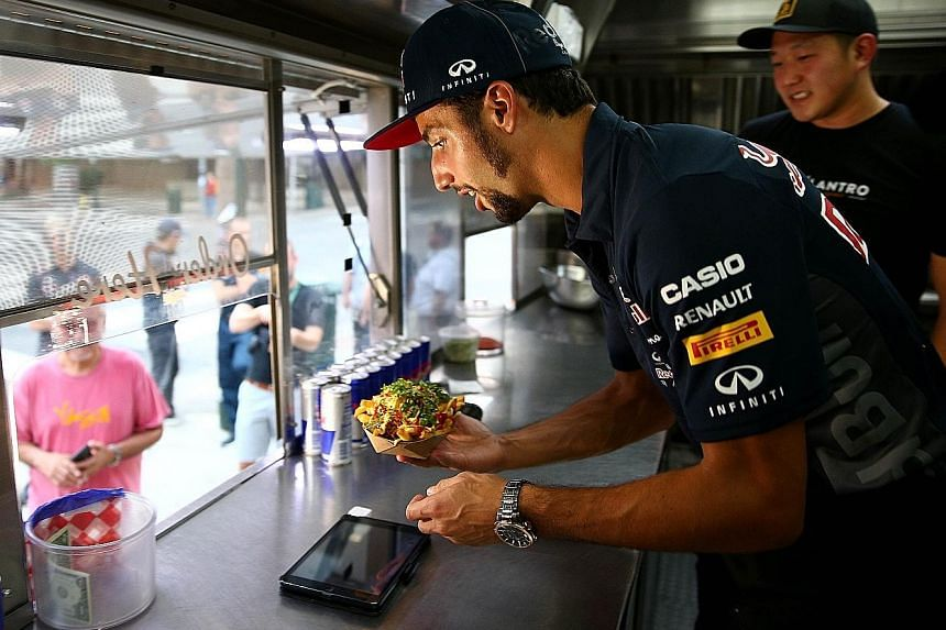 Red Bull driver Daniel Ricciardo of Australia displaying a separate set of skills while serving a customer at a food truck in Austin, Texas, on Thursday.