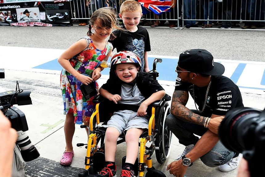 Lewis Hamilton with young fans on Thursday before the US Grand Prix. Winning a third world championship would place him on par with some of the sport's greats like Jack Brabham, Jackie Stewart, Niki Lauda, Nelson Piquet and Ayrton Senna.