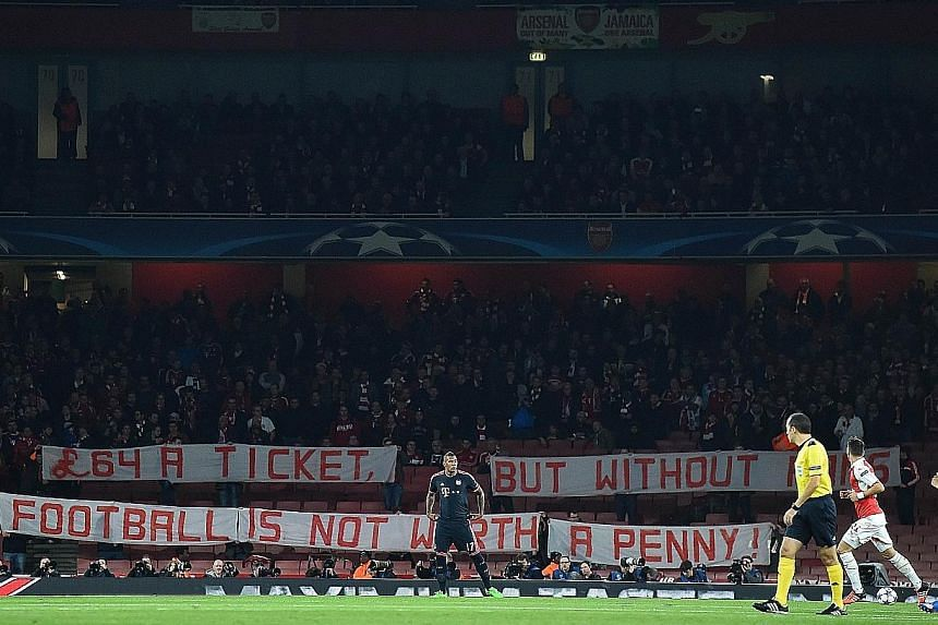 Bayern fans holding a banner in protest against the high cost of tickets, at the beginning of the Champions League match against Arsenal. They had each forked out about S$400 for the entire trip.