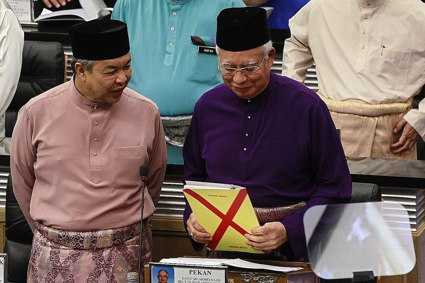 Malaysian Prime Minister Najib Razak holding the Budget draft as he spoke to DPM Ahmad Zahid Hamidi before addressing the MPs at Parliament House in Kuala Lumpur yesterday.