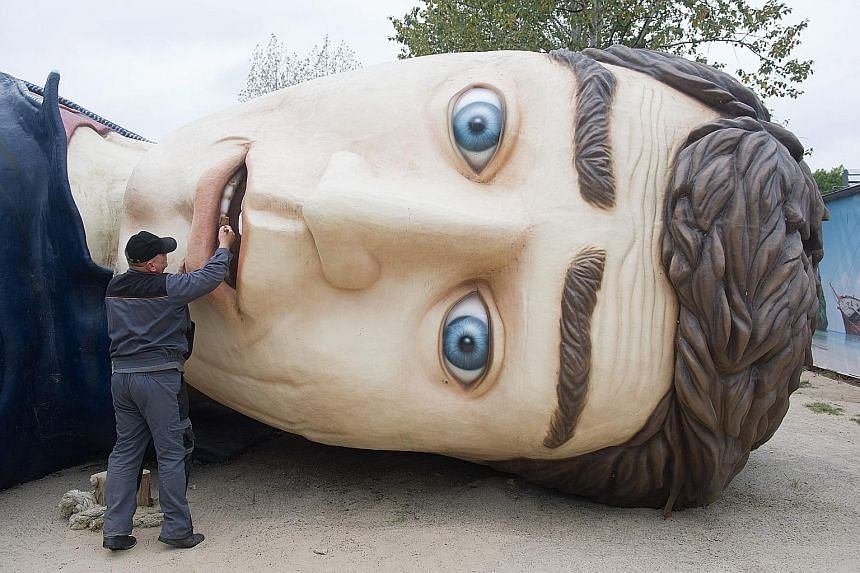 """A worker cleaning the teeth of """"Gulliver"""" at the Gulliver's World adventure park on Germany's Usedom Island. The sculpture of Gulliver - the character in Jonathan Swift's famous novel Gulliver's Travels - requires cleaning to avoid weather damage dur"""