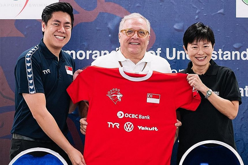 Edwin Ker (left), Singapore Swimming Association (SSA) executive director, and Bob Gambardella (centre), Singapore Sports Institute chief, presenting Goy Soon Lan, Republic Polytechnic's (RP)'s director, School of Sports, Health & Leisure, with a tok