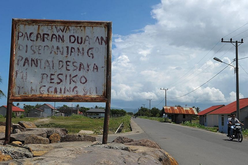 """A board in Banda Aceh, Indonesia, reads: """"If you date on the beach, the risk is your own."""" Aceh province, the only part of Indonesia that is allowed to implement Islamic law, carries out public canings for a variety of infringements. It is now cracki"""