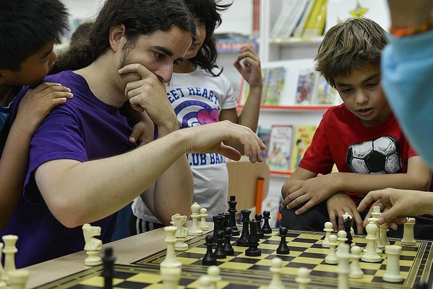 Pupils playing chess with their teacher at a public school in Madrid. Some studies have shown that an hour of chess a week can boost pupils' performance in maths by 30 per cent.
