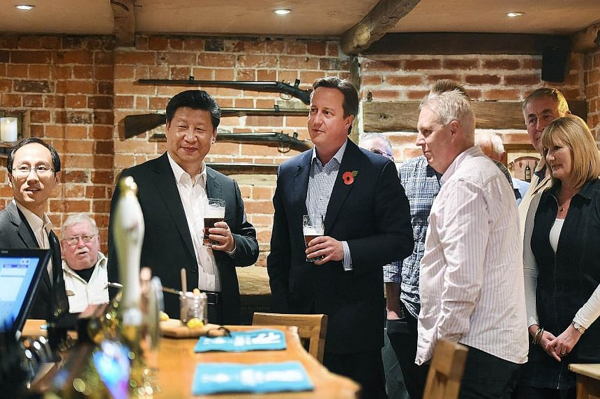 Chinese President Xi Jinping (third from left) having beer with British Prime Minister David Cameron at a traditional British pub on Thursday during his state visit. The two leaders, in suits but not wearing ties, were at The Plough, not far from the