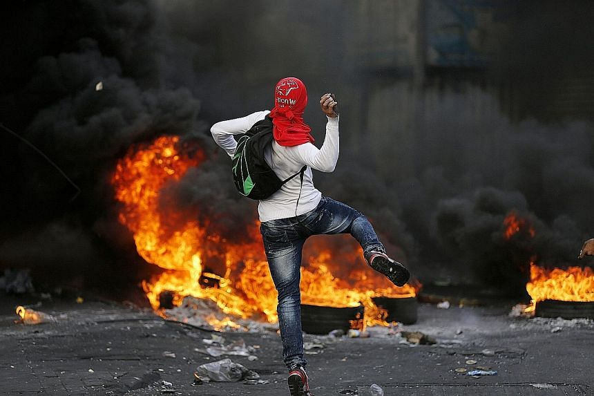 A Palestinian protester hurling stones at Israeli soldiers during a clash in the West Bank city of Hebron this week. About 60 people have been killed in the current wave of violence.