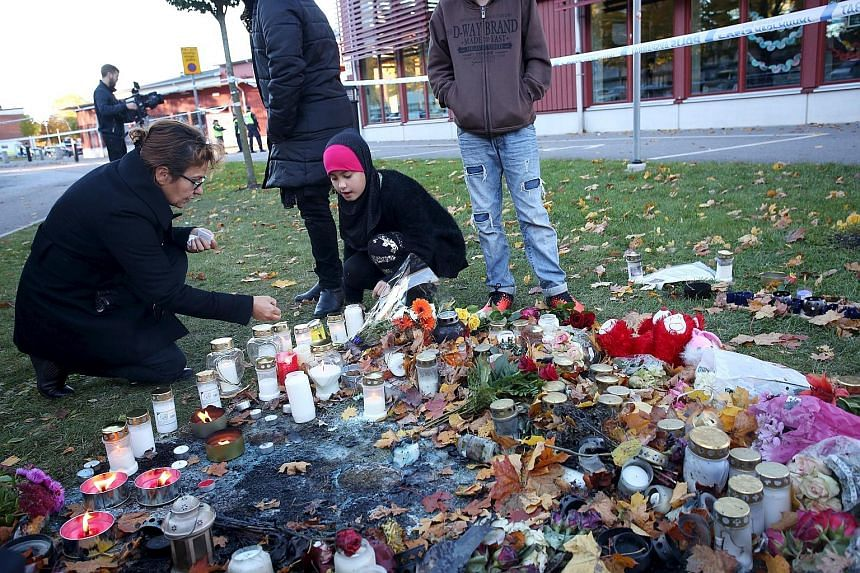 People lighting candles yesterday outside the Kronan School in Trollhattan, an industrial town in western Sweden with a large immigrant population. In Thursday's attack, the 21-year-old masked swordsman (above, right) walked through the school, stabb