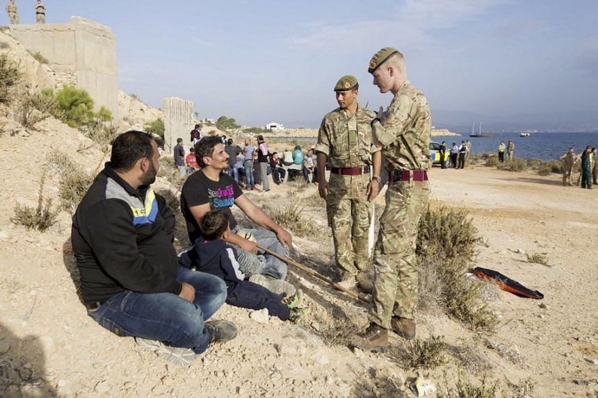 British soldiers speak to migrants on a beach at Royal Air Force base Akrotiri in Cyprus on Oct 21 2015.