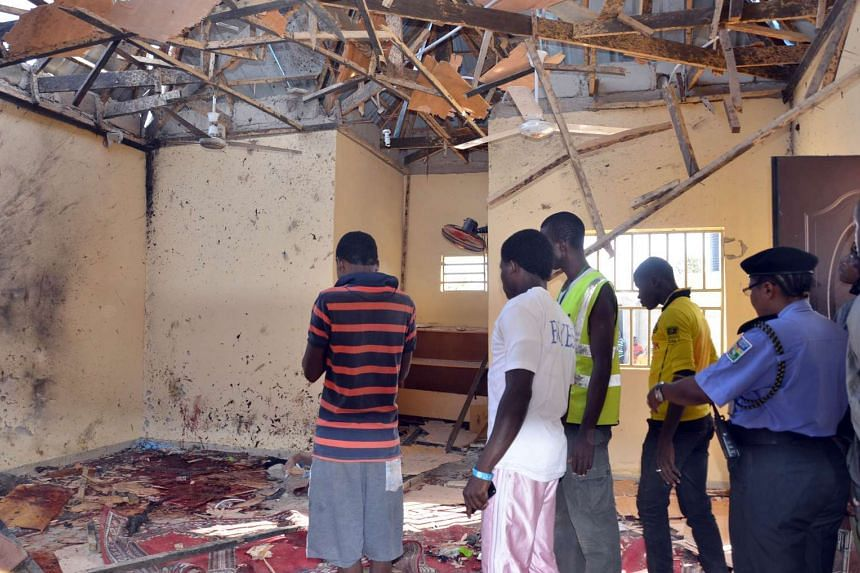 At least 28 people were killed in a separate suicide bombing at a mosque (above) in Maiduguri, north-east Nigeria, on Friday.