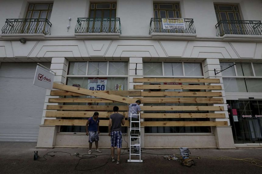An employee boards up the windows of a store as Hurricane Patricia approaches the Pacific beach resort of Puerto Vallarta.