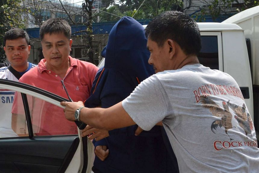 Shooting suspect Li Qing Liang is escorted out of a police detention centre in Cebu city on Oct 23, 2015.