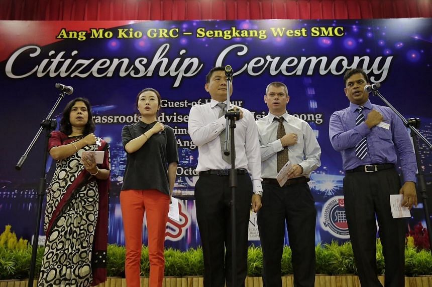 New citizens, Madam Ramakrishnan Jayachitra (extreme left), Ms Wu Qi (in black), Mr Jayaram Amoss (in blue) and Mr Zawadzki Darius Andrzej (second from right) are led by a grassroots leader in reciting the National Pledge.