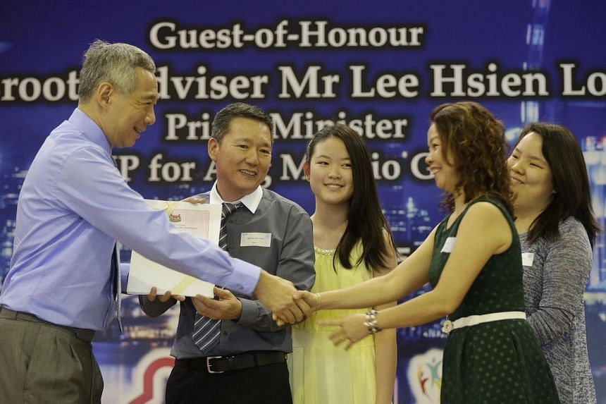 Prime Minister Lee Hsien Loong (extreme left) gives out citizen certificates to Madam Chiam Soo Nai (second from right), 50, her husband, Mr Low Cher Hong (second from left), 51, and their daughters.