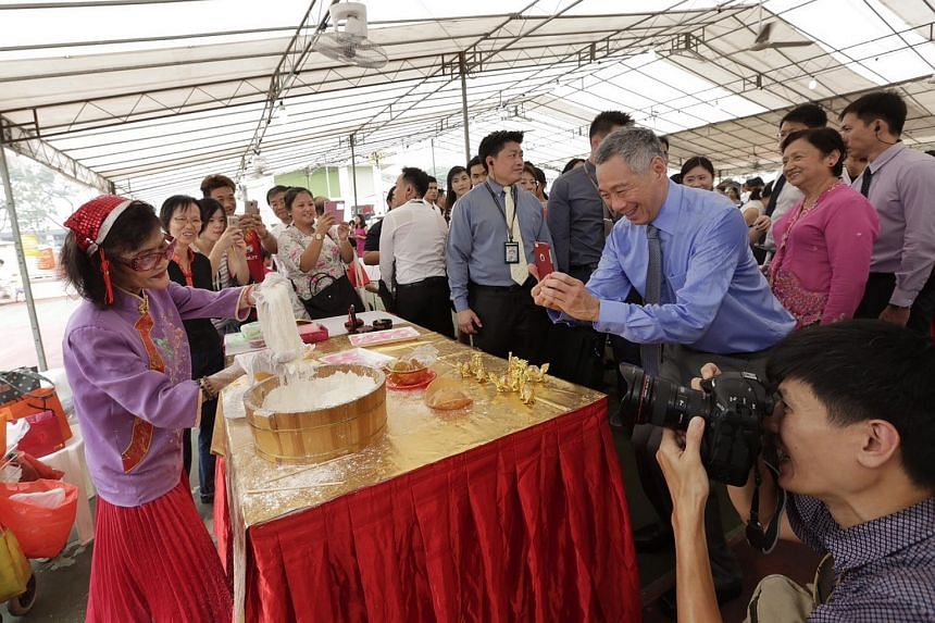 Prime Minister Lee Hsien Loong (in blue) takes a photograph of Madam Lily Ho (extreme left) at the Chinese cultural booth after the citizenship ceremony held at Teck Ghee Community Club.