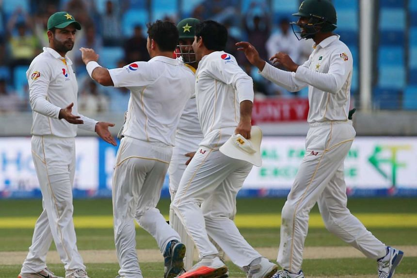 Pakistan players celebrate after dismissing England's Alastair Cook on Day 2 of their second Test cricket match in Dubai on Oct 23, 2015.